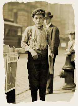Newsboy holding newspapers and standing next to a paper stand on a commercial street, 1904